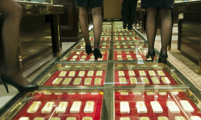 Chinese sales staff walk along an aisle paved with gold bars at a gold exchange house in Kunming, China, Dec. 11, 2012. (STR/AFP/Getty Images)