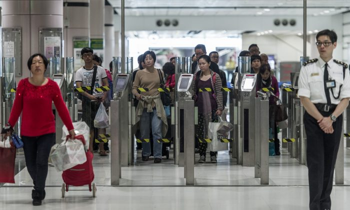 People proceed to an immigration check at a border crossing point with mainland China in Hong Kong on March 1, 2013. Chinese citizens who fall into certain disfavored groups—such as political activists—are regularly barred from entering China. (Philippe Lopez/AFP/Getty Images)