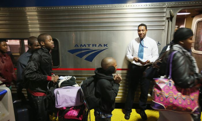 Train attendant Jared Wright helps passengers board Amtrak's Southwest Chief in Union Station bound for Los Angeles on April 9 in Chicago. Train travel is having a revival, with March breaking ridership records for Amtrak. (Scott Olson/Getty Images)