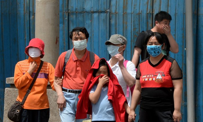 People wear masks to protect against air pollution and dust in Beijing on May 19, 2013. (Mark Ralston/AFP/Getty Images)