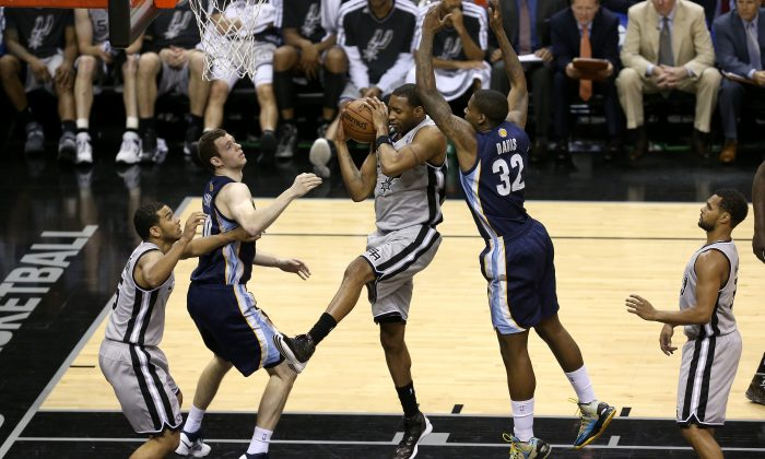 Tracy McGrady #1 of the San Antonio Spurs grabs a rebound against Ed Davis #32 of the Memphis Grizzlies during Game One of the Western Conference Finals of the 2013 NBA Playoffs at AT&T Center on May 19, 2013 in San Antonio, Texas. (Stephen Dunn/Getty Images)