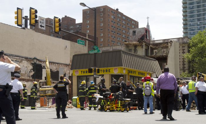 Rescue workers search for victims and clear debris from a building that collapsed at a demolition site, at 22nd and Market Streets, June 5 in Philadelphia, Pennsylvania. The building being demolished landed on top of a Salvation Army Thrift Store. (Jessica Kourkounis/Getty Images)