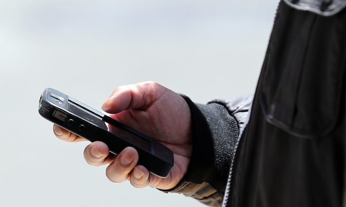 A pedestrian uses a smartphone as he walks along Market Street on June 5, 2013 in San Francisco. A leaked secret order apparently reveals that the NSA is collecting call records on a daily basis from Verizon (Justin Sullivan/Getty Images)