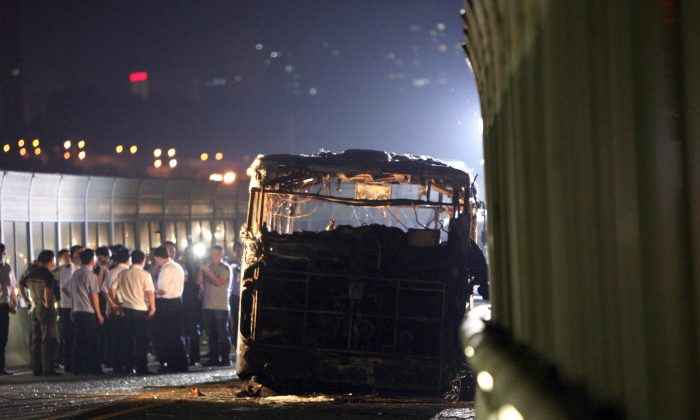 This picture taken on June 7, 2013 shows investigators at the scene of a bus that caught fire on the BRT (Bus Rapid Transit) elevated road in the city of Xiamen, China's southeast Fujian province. A fire that engulfed a commuter bus in minutes during rush hour in the Chinese city of Xiamen, killing 47 and injuring dozens more, appears to have been deliberately set, state media quoted investigators as saying on June 8. (STR/AFP/Getty Images)