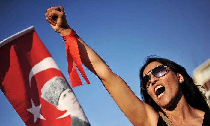 A protester raises her fist and shouts a slogan during a demonstration on Gundogdu Square in Izmir on June 9, 2013. (Ozan Kose/AFP/Getty Images)