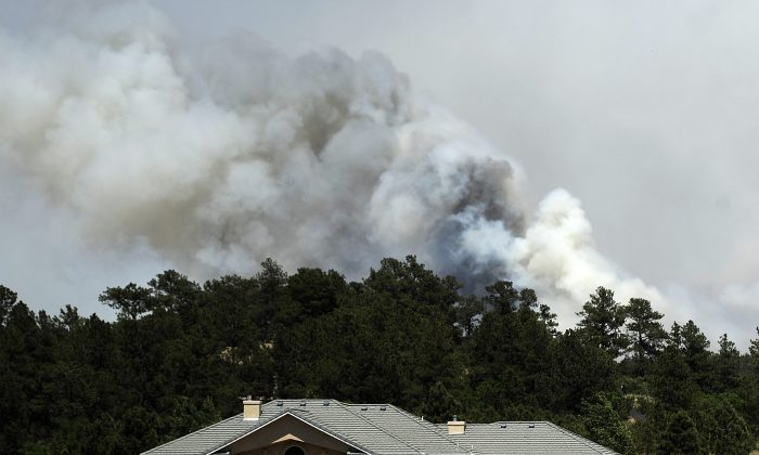 Smoke fills the air from the Black Forest Fire near Colorado Springs, Colorado on Wednesday, June 12, 2013. Many residents, including John Bissett, the president of the Housing and Building Association of Colorado Springs, had to evacuate their homes to find shelter with friends or in their motorhomes. (Photo by Chris Schneider/Getty Images)