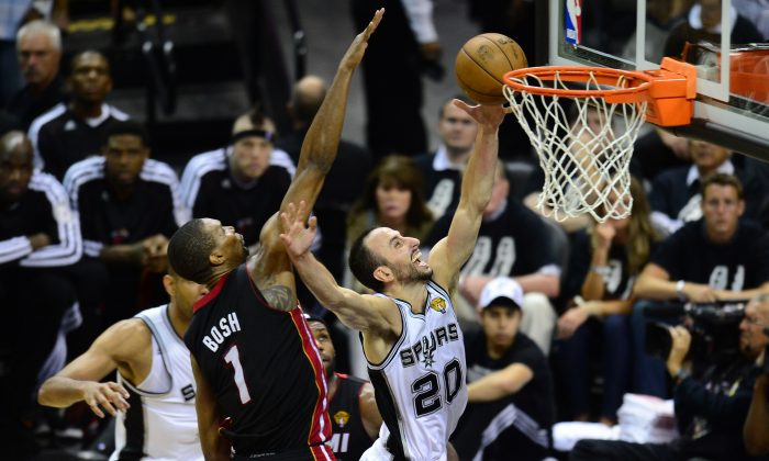 Manu Ginobili of the San Antonio Spurs scores under pressure from Chris Bosh of the Miami Heat during game 5 of the NBA finals on June 16, 2013 in San Antonio, Texas., where the Spurs defeated the Heat 114-104 and now lead the series 3-2. (Frederic J. Brown/AFP/Getty Images)