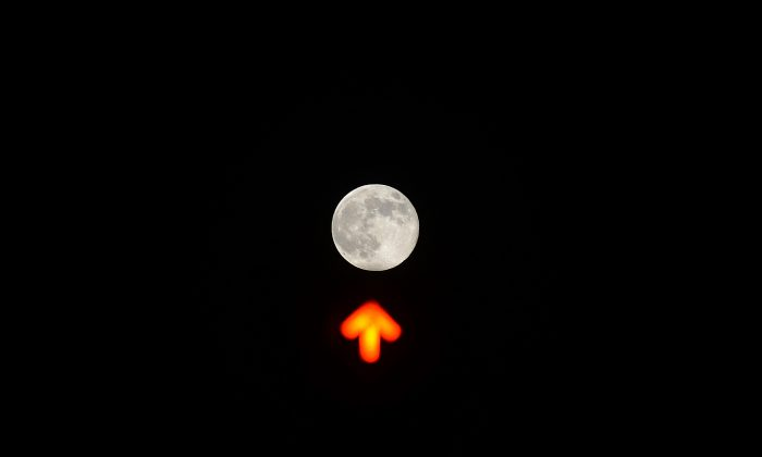 A picture shows the moon over a traffic light in downtown Rome on June 23, 2013.  (FILIPPO MONTEFORTE/AFP/Getty Images)