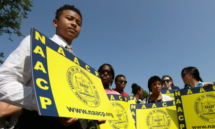 Supporters of the National Association for the Advancement of Colored People (NAACP) hold signs outside the U.S. Supreme Court building on June 25 in Washington, D.C. The court ruled that Section 4 of the Voting Rights Act, which aimed at protecting minority voters, is unconstitutional. (Win McNamee/Getty Images)
