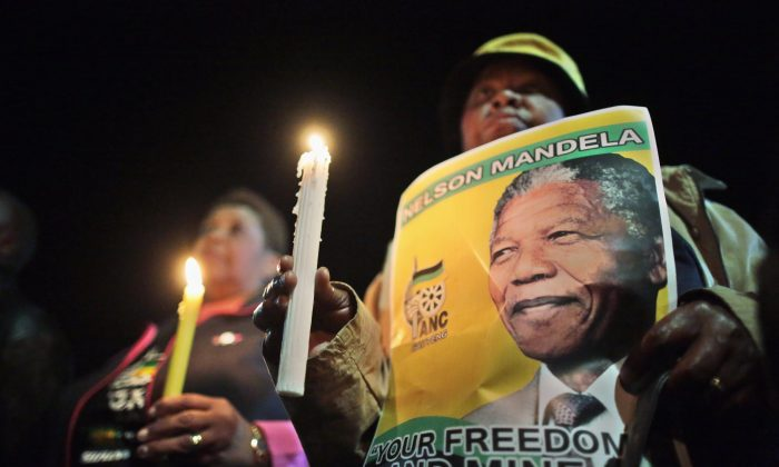 Supporters hold a candlelit vigil outside the former home of former South African President Nelson Mandela in Soweto township on June 27, 2013 in Johannesburg, South Africa. South African President Jacob Zuma confirmed on June 23 that Mandela's condition has become critical since he was admitted to the hospital over two weeks ago for a recurring lung infection. (Christopher Furlong/Getty Images)