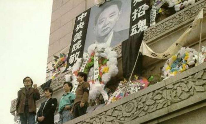 APRIL 18: Students hold aloft a banner calling for 'Freedom & Democracy Enlightenment' on the Martyr's Monument in Tiananmen Square festooned with a large portrait of Hu Yaobang, surrounded with wreaths dedicated to him by people from many universities. (64memo.com)