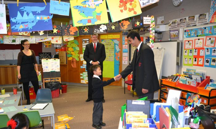 Year 10 student John Dibah (R) from Northside Christian College on his one day as shadow principal shakes a kindergarten students hand as he visits the class with Principal Stephen Leslie (Centre). (Jianguo Wu/The Epoch Times)
