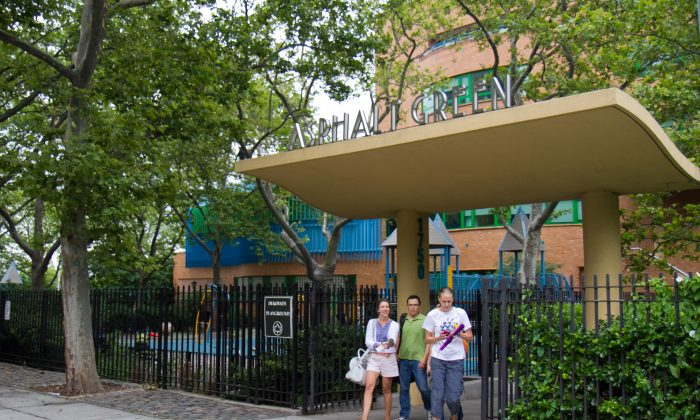 People walk out of the Asphalt Green Community Center on Manhattan's Upper East Side, where the city's proposed marine transfer station would be built—directly behind the center. (Benjamin Chasteen/The Epoch Times)