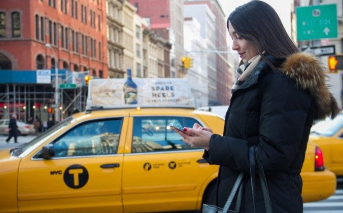 A woman uses her cellphone in front of a yellow taxi in Manhattan. A state supreme court lifted a restraining order on the e-hail program on June 6, which prohibited smartphone apps that allowed users to hail taxis. (Ben Chasteen/The Epoch Times)