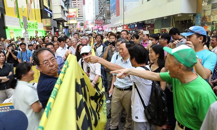 Lam Kwok-on, left, is pointed out by onlookers, after attempting to use his banner to block those belonging to Falun Gong practitioners. The altercation between the Communist Party front group and Falun Gong practitioners is the first major incident since the authorities cracked down on the HCKYCA's banner presence in Hong Kong. (Pan Zaishu/Epoch Times]