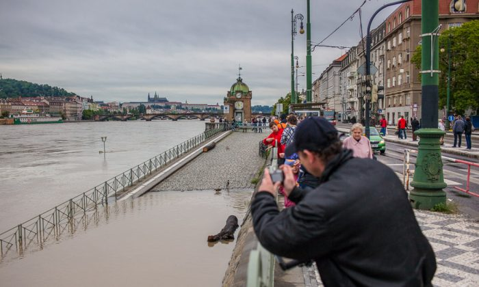 A man takes a picture of the flooded Vltava River, Prague, Czech Republic, June 3, 2013. (Petr Svab/Epoch Times)