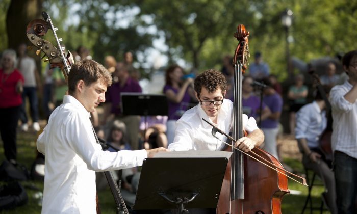 Double bass players get ready to perform in Central Park, June 22. (Samira Bouaou/Epoch Times)