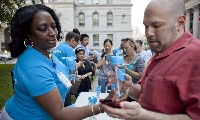 People download the NYC Water app on their phone in exchange for a free water bottle at City Hall Park, June 22. (Samira Bouaou/Epoch Times)