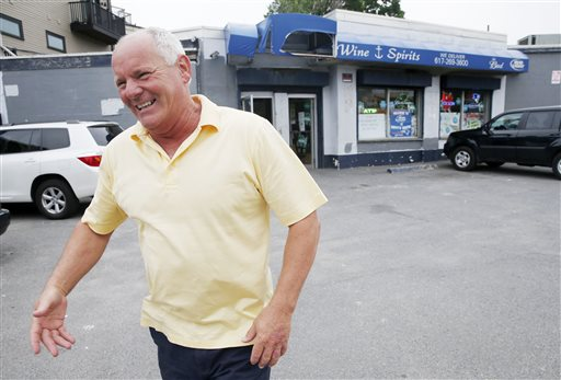 """Stephen Rakes smiles after greeting an acquaintance outside the liquor store he once owned in the South Boston neighborhood of Boston, Thursday, June 6, 2013. Four decades after Boston crime boss James """"Whitey"""" Bulger first rose to power, """"Southie"""" is not what it used to be. The once blue-collar, Irish-Catholic neighborhood, is now an ethnic melting pot that has been invaded by young urban professionals who have gentrified the area and smoothed out its once-rough edges. (AP Photo/Michael Dwyer)"""