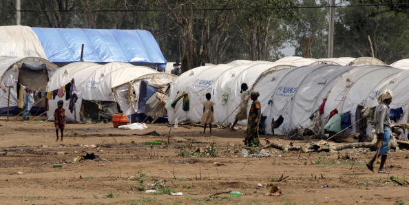 Tamil civilians walk near their tents at the Manik Farm refugee camp located on the outskirts of the northern Sri Lankan town of Vavuniya on May 26, 2009.  Australia remains a preferred destination for many Tamil Srilankan refugees who get smuggled from Srilanka and India into Canberra on boats. (DAVID GRAY/AFP/Getty Images)