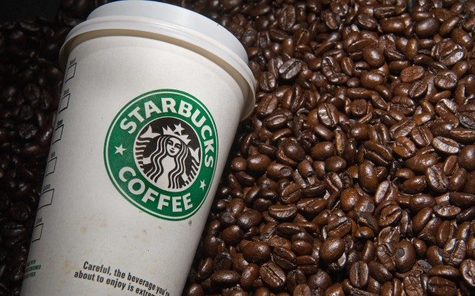 A Starbucks coffee cup and beans are seen. (Paul J. Richards/AFP/Getty Images)