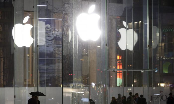 Pedestrians pass the Apple store location on fifth avenue Thursday, June 6, 2013, in New York. The United States is investigating a possible price fixing of E-Books in Apple's favor. (AP Photo/Frank Franklin II)