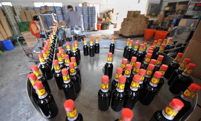 Workers inspect bottles of Kowloon Soy Sauce at their factory in the New Territories area of Hong Kong on December 15, 2008. (TED ALJIBE/AFP/Getty Images)