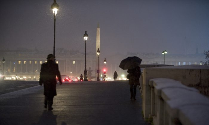 People walk on the snow-covered Pont de la Concorde in Paris on December 17, 2009. Many have witnessed public streetlights that mysteriously go dark as someone passes below.  Over the years, as these individuals have begun to share their experiences, this phenomenon has come to be known as Street Light Interference (SLI). (Fred Dufour/AFP/Getty Images)