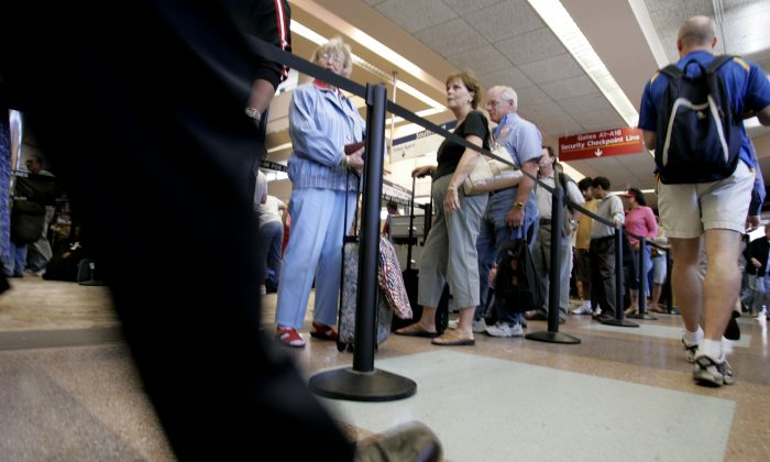 Airline passengers wait in a long line at a security checkpoint at San Jose International Airport in San Jose, Calif. in this file photo. (AP Photo/Paul Sakuma)