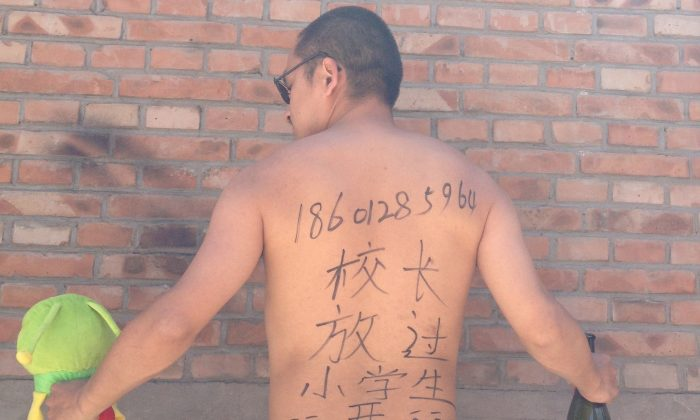 "Beijing-based poet Wang Zang poses at his workplace in Beijing with the Chinese characters ""Principal, get a room [with me]. Leave the young students alone."" scribbled on his back while holding a stuffed animal and a liquor bottle, on May 29, 2013. Artists, activists, university students, and police officers are photographing themselves—some nude and provocatively posed, some angry and menacing—with the same message. (AP Photo/Courtesy of Wang Zang)"