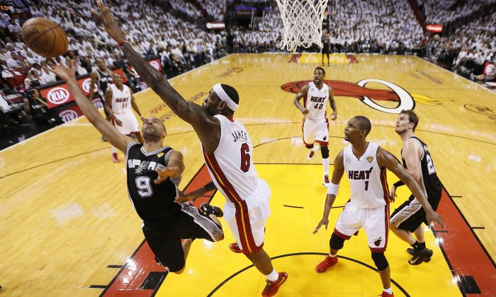 San Antonio Spurs point guard Tony Parker (9) heads to the hoop as Miami Heat small forward LeBron James (6) defends during the first half of Game 1 of basketball's NBA Finals, Thursday, June 6, 2013 in Miami. (AP Photo/Mike Ehrmann, Pool)