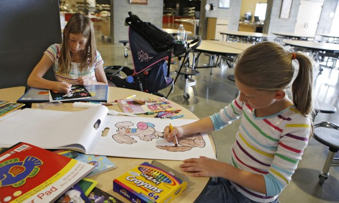 Brook Cramer, right, 9, and her sister Taylor, 11,  color at the American Red Cross shelter in Monument, Colo., for evacuees from the nearby Black Forest wildfire on Friday, June 14, 2013. The sisters are among nearly 4,000 people are still evacuated from the fire that broke out on Tuesday. (AP Photo/Ed Andrieski)