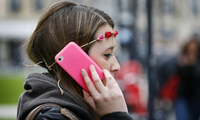 A woman makes a phone call on a brightly coloured smartphone in Bordeaux, France, on May 3, 2013. Under new CRTC rules announced Monday, cellphone customers will be able to leave their contracts after two years without any early-cancellation penalties. (Patrick Bernard/AFP/Getty Images)