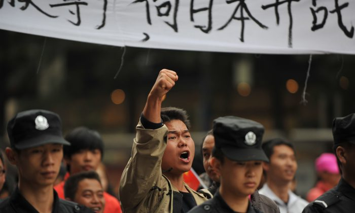 "A Chinese demonstrator shouts slogans during a protest against Japan's ""nationalizing"" of Diaoyu Islands, also known as Senkaku in Japan. This protest was in Kunming, in southwest China's Yunnan province, on September 18, 2012.Thousands of anti-Japan protesters rallied across China over a territorial row on September 18, a key historical anniversary, as Japanese firms including car giant Toyota shut or scaled back production. (STR/AFP/GettyImages)"
