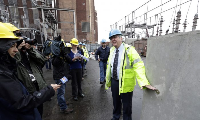 Con Edison's Chairman and CEO, Kevin Burke, points to where the flood waters reached during Superstorm Sandy on a wall put up to protect a relay house at the Mill Yard substation during a news conference to announce investments made to protect its energy delivery systems from major storms Tuesday, May 28, 2013, in New York. (AP Photo/Frank Franklin II)
