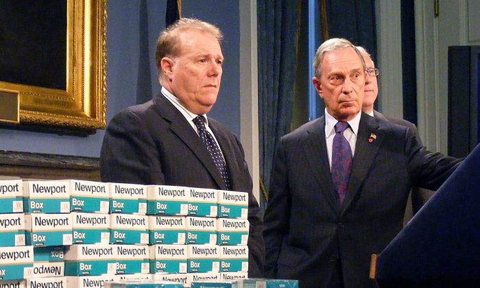 New York City Mayor Michael Bloomberg and former chief policy adviser John Feinblatt present untaxed cigarette packs that were captured in an undercover operation at the Poospatuck Reservation on Long Island in this 2010 file photo. A group of New York City businesses is calling for a war on black market cigarettes, which is the source of an estimated 60 percent of cigarettes in New York City. (Gidon Belmaker/Epoch Times)