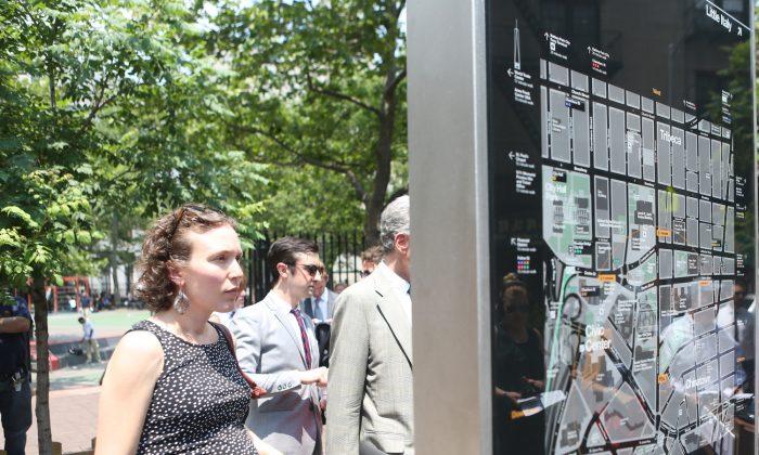 A woman views a WalkNYC pedestrian map in Manhattan's Chinatown on June 24, 2013. (Gary Du/Epoch Times)
