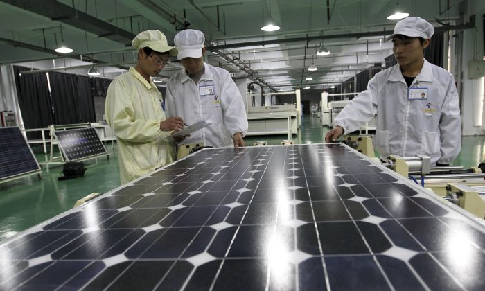 Chinese workers examine solar panels at a manufacturer of photovoltaic products in Huaibei in central China's Anhui province on March 21, 2012. The European Union announced Tuesday, June 4, 2013 that it is to impose anti-dumping levies on imports of Chinese solar panels. The Chinese responded by hitting back with restrictions on European wine importa. (AP Photo/File)