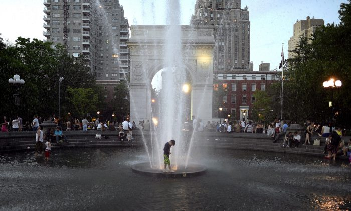 FOUNTAIN OF COOL: Kids takes advantage of the hot weather as they play in the fountain at dusk at Washington Square Park May 31, 2013 as temperatures reach in the 90's in New York City. (Timothy Clary/AFP/Getty Images)