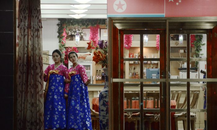 Hostesses wait for customers at the entrance to a Korean restaurant in Dandong in China's northeastern Liaoning Province, on Dec. 12, 2012. Growth in China's restaurant industry slowed by almost 40 percent in 2012. (Wang Zhao/AFP/Getty Images)