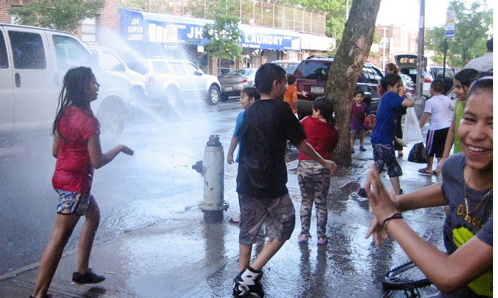 Kids take a break from the heat by playing in the cool water of an open fire hydrant in Jackson Heights, Queens, on June 1. (Joshua Philipp/The Epoch Times)