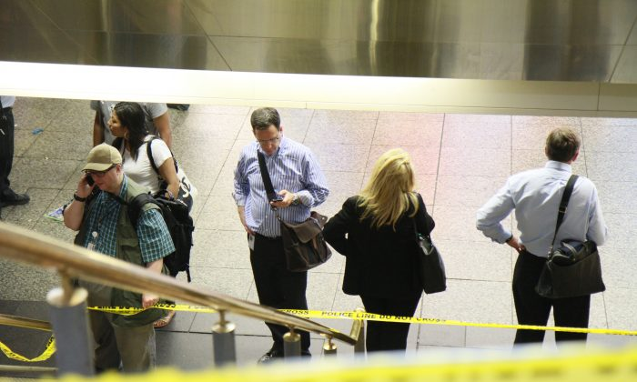 Commuters stand by police tape in Penn Station on June 17, 2013. (Ivan Pentchoukov/Epoch Times)