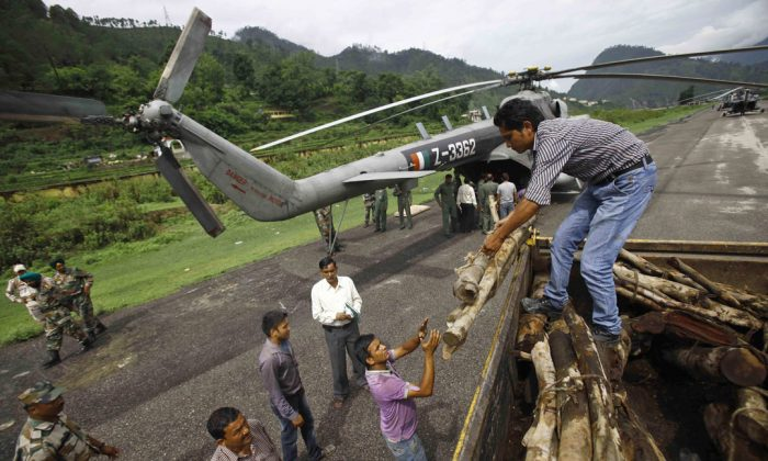 Locals unload woods from a truck going on an Indian air force helicopter, in Gauchar, in northern Indian state of Uttarakhand, Tuesday, June 25, 2013. On Tuesday authorities started the mass cremation of flood victims amid fears of spreading an epidemic. (AP Photo/Rafiq Maqbool)