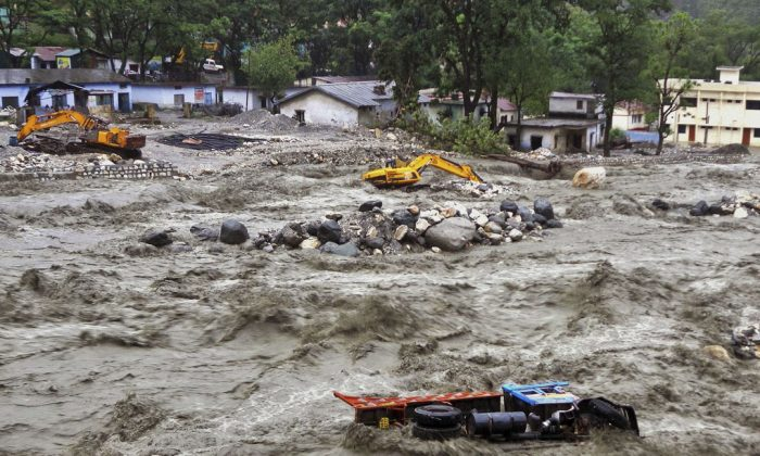 A bulldozer and other vehicles drift in a flooded river in Uttarkashi District, India, Monday, June 17, 2013. Torrential rains and floods washed away buildings and roads. Thousands are feared dead and nearly 60,000 are stranded.  (AP Photo)