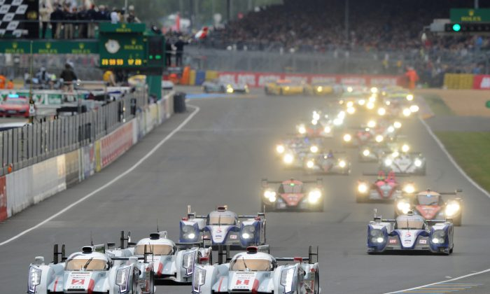 Audi R18 e-tron quattro #2 driven by Allan Mc Nish (L) races team mate André Lotterer in the #1 R18 e-tron quattro (R Front) ahead of Lucas Di Grassi in the #3 Audi (2L), all three ahead of the Toyotas of Nicolas Lapierre (3L) and  Anthony Davidson (R) at the start of the Le Mans 24 Hour Race on June 22, 2013, in Le Mans, France. (Jean Francois Monier/AFP/Getty Images)