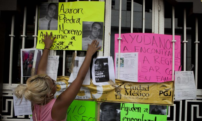 Friends put pictures in the bar entrance of their recently disappeared relatives in Mexico City, May 30, 2013. (AP Photo/Eduardo Verdugo)