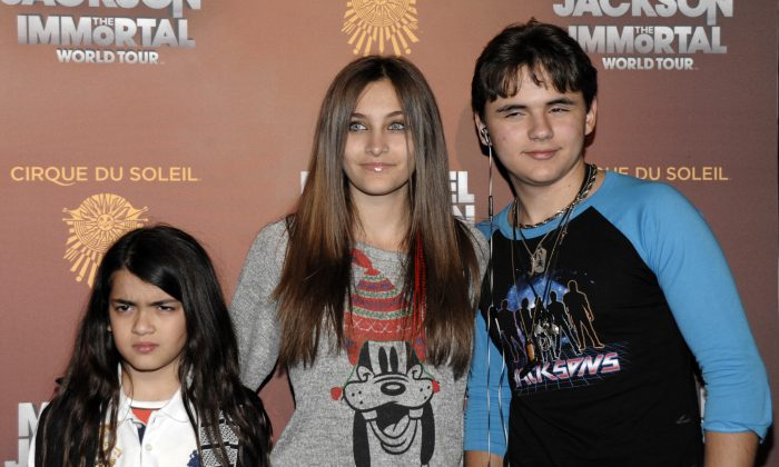 (L-R) Blanket Jackson, Paris Jackson, and Prince Michael Jackson at the opening night of the Michael Jackson The Immortal World Tour in Los Angeles, Jan. 27, 2012.  (AP Photo/Dan Steinberg)