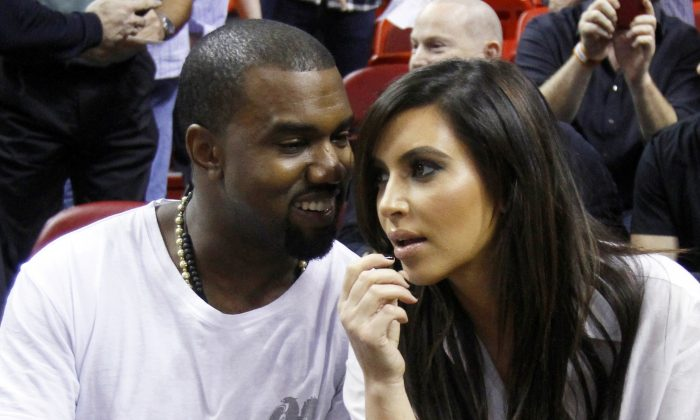 This Dec. 6, 2012 file photo shows singer Kanye West, left, talks to his girlfriend Kim Kardashian before an NBA basketball game between the Miami Heat and the New York Knicks in Miami. (AP Photo/Alan Diaz)