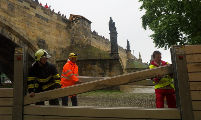 Emergency services workers build anti-flood barriers on the left bank of Vlatva River near the Charles Bridge in Prague, Czech Republic on June 2, 2013. After another night of downpours in the capital and elsewhere in the Czech Republic the water in Vltava is expected to reach critical levels on June 3, 2013.  (Michal Cizek/AFP/Getty Images)