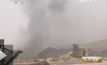 A screenshot from a recent China Central Television report shows coal dust billowing from piles of coal in Zhangjiakou, Hebei Province. This dust has not only polluted the air, but also turned the apples black. (CCTV screenshot via the Epoch Times)